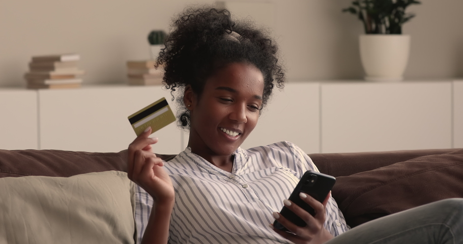 Young african woman rest on couch hold smartphone and credit card enjoy easy instant money transfer, makes good deed on-line donation secure payment. Happy customer and online retail services concept Royalty-Free Stock Footage #1065237316