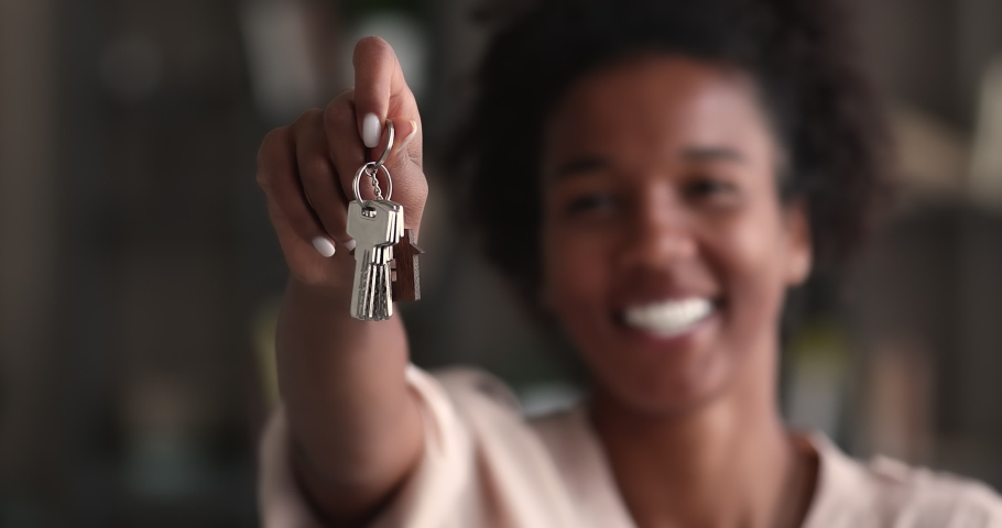 Mixed-race woman holding keys, close up focus on hand. Realtor real estate agent selling property, make special offer of affordable dwelling, relocation day, happy homeowner person, bank loan concept | Shutterstock HD Video #1065237850