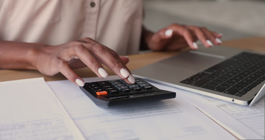 African woman sit at desk calculates costs using calculator and laptop, close up view. Female manage expenditures, control personal expenses, pay through e-bank app. Business accounting work concept Royalty-Free Stock Footage #1065237958