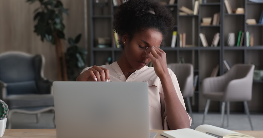 Tired african woman take off glasses resting from laptop work. American businesswoman suffers from dry irritable eyes after long notebook usage. Eye strain, conjunctivitis infection need drops concept Royalty-Free Stock Footage #1065238144