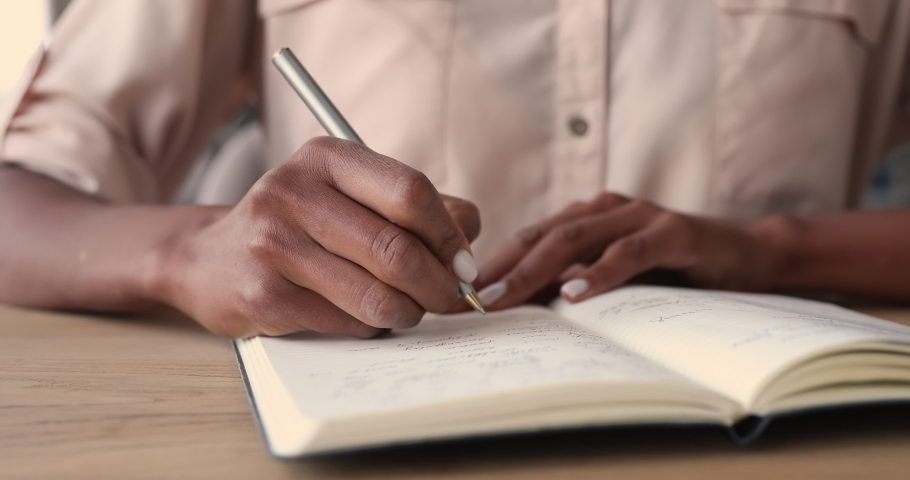 African woman sitting at desk holding pen making notes in diary, close up view. Businesswoman writes startup business ideas and plans, creative thoughts to notebook. Create to-do or wish list concept Royalty-Free Stock Footage #1065238201