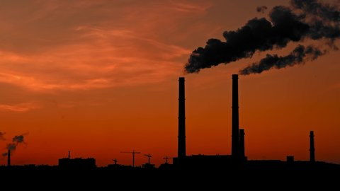 Powerful smoke coming out of pipes on a red sunset