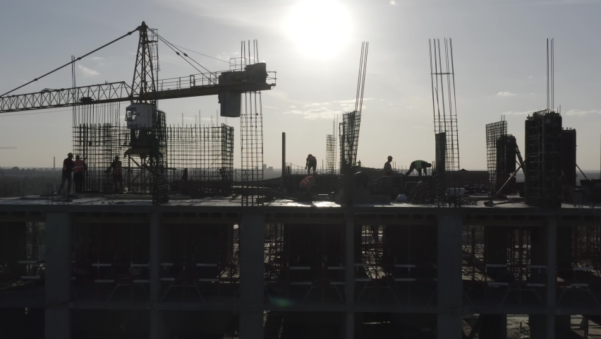 Construction workers (builders) silhouettes are on the rooftop of a residential building under construction (in a course of building). Aerial side view Royalty-Free Stock Footage #1065264562