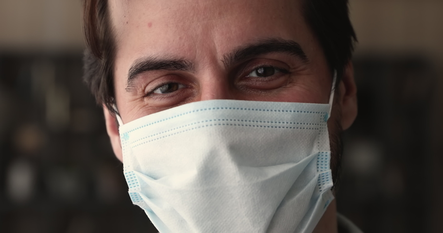 Close up portrait smiling 35s man wear disposable surgical face mask standing indoor looking at camera. Facemask sign of awareness, personal safety due covid-19 pandemic outbreak, protection concept