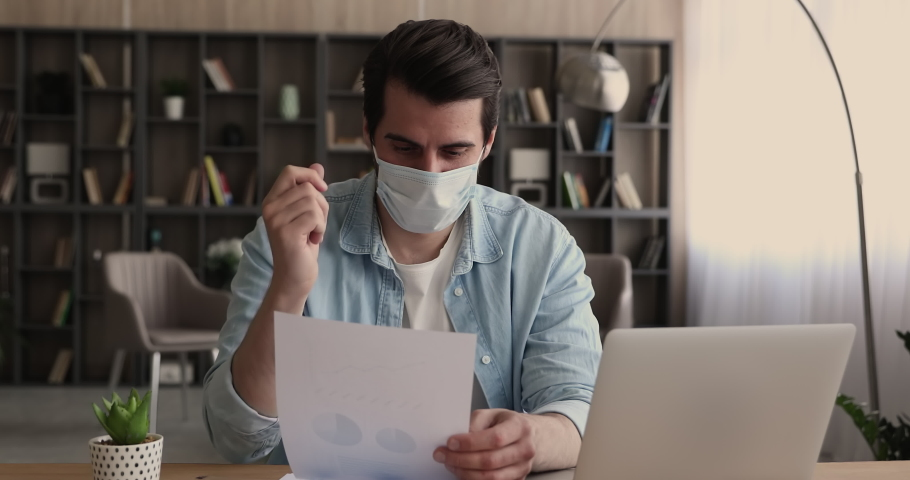 Employee in protective disposable facemask sit at workplace use laptop prepare report, hold document paper makes presentation, analyzing statistics sales data. Analysis, strategizing, planning concept Royalty-Free Stock Footage #1065266560