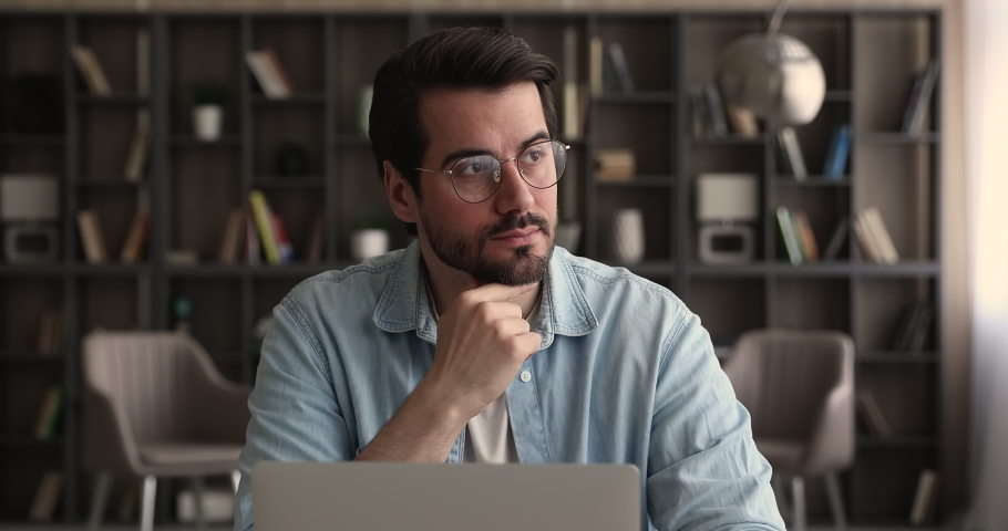 Pensive business man in glasses distracted from laptop work pondering looks in distance. Thoughtful employee search creative ideas, think on challenge seated at desk. Planning, business vision concept Royalty-Free Stock Footage #1065266671