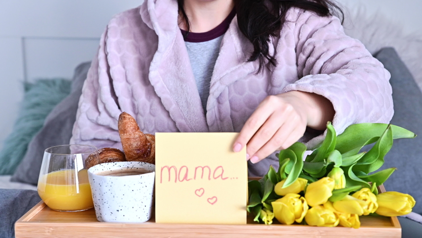 Young woman opens a postcard with a stack of mom in English. Breakfast, coffee and flowers for mom in the morning in bed. Surprise on mom's day from children. High quality 4k footage