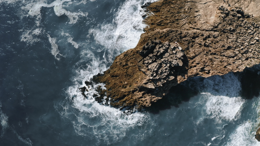 ocean waves hit the rock, rotating topshot aerial view in Portugal. High quality 4k footage