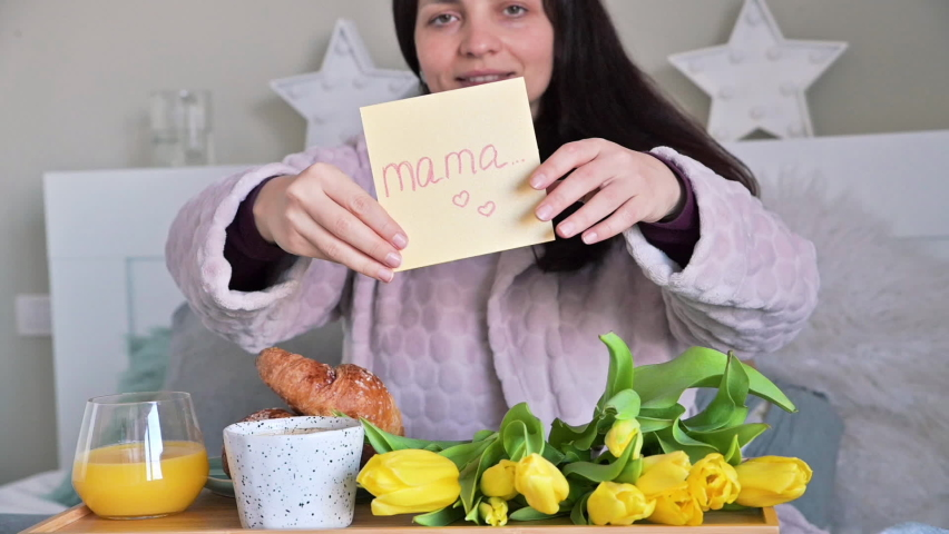 Mom holds a greeting card and a bouquet of flowers. Happy young woman received a surprise on womens day 8 march. Breakfast in bed for mom. English text - Mom. High quality FullHD footage