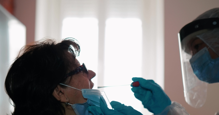A lab technician in a protective suit takes a swab from a grandma patient for coronavirus at home.  Doctor at home. PCR throat sample for corona virus test by medicine nurse indoors.  Royalty-Free Stock Footage #1065291109