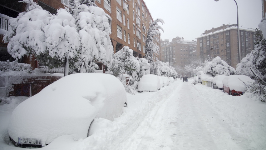 MADRID (SPAIN) - January 9 2021 Wide shot of a person walking in Madrid under the snow in the middle of a street covered by snow with parked cars buried in snow after storm Filomena hit Spain