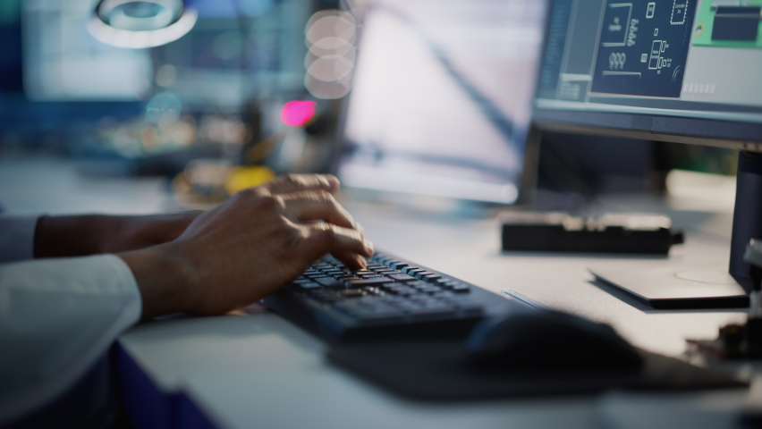 Modern Electronics Research, Development Facility: Engineer Working on Computer, Typing with His Hands on a Keyboard. Scientist Design PCB, Silicon Microchips, Semiconductors. Closeup Focus on Hands Royalty-Free Stock Footage #1065341833
