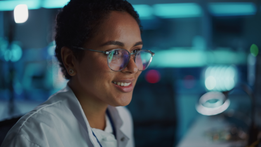 Portrait of Beautiful Black Latin Woman Computer Screen Reflecting in Her Glasses. Young Intelligent Female Scientist Working in Laboratory. Background Bokeh Blue with High-Tech Technological Lights