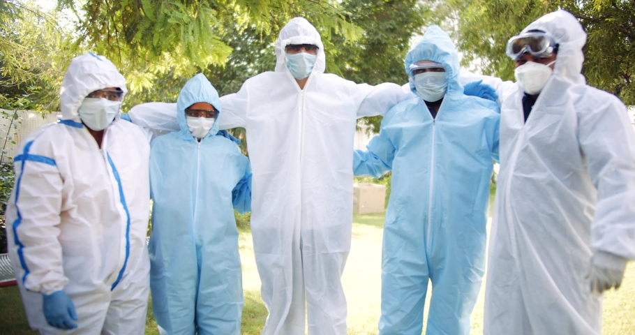 Handheld slow-motion of young medical staff, females males, in full body ppe suits outdoors India come togetherness bond share excited ecstatic celebrate victory looking at camera pov Royalty-Free Stock Footage #1065348229