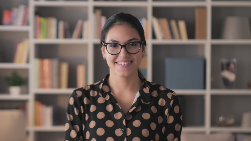 Portrait of middle eastern young business woman smiling to the camera,head shoulder shot of brunette female entrepreneur wearing glasses smiling confident looking the cam
