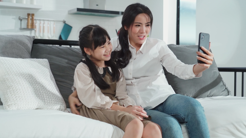 Asian family little kid girl and mother talking in video conference by smartphone together in living room at home with happiness and smile. Happy activity technology lifestyle mobile phone use concept | Shutterstock HD Video #1065376846