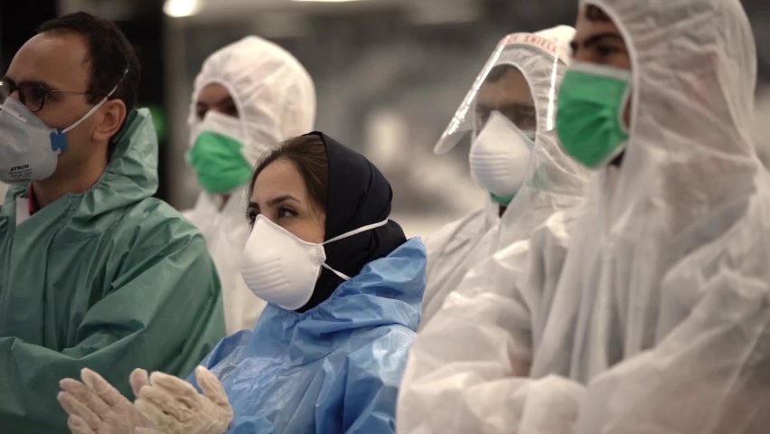 A group of female and male health care staff with face mask and protective gear and gloves clapping for medical staff support during coronavirus pandemic time. portrait of men and women | Shutterstock HD Video #1065385927