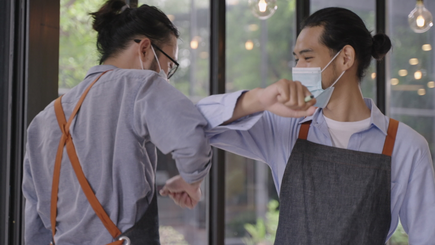Young Asian man wearing protective face mask while working in restaurant or cafe and greeting his colleague by elbow touch. Alternative greeting for prevent spread of coronavirus infection.