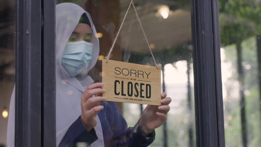 Young Asian Muslim woman wearing face mask, turning sign to closed the coffee shop or restaurant due to coronavirus crisis. Female Muslim business owner changing sign from open to closed. Royalty-Free Stock Footage #1065443026