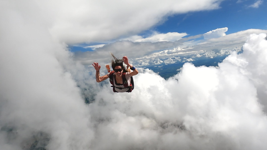 Video of a young woman parachutist smiling in free fall. Perfect concept of happiness and freedom. 59,94 fps in 4K resolution