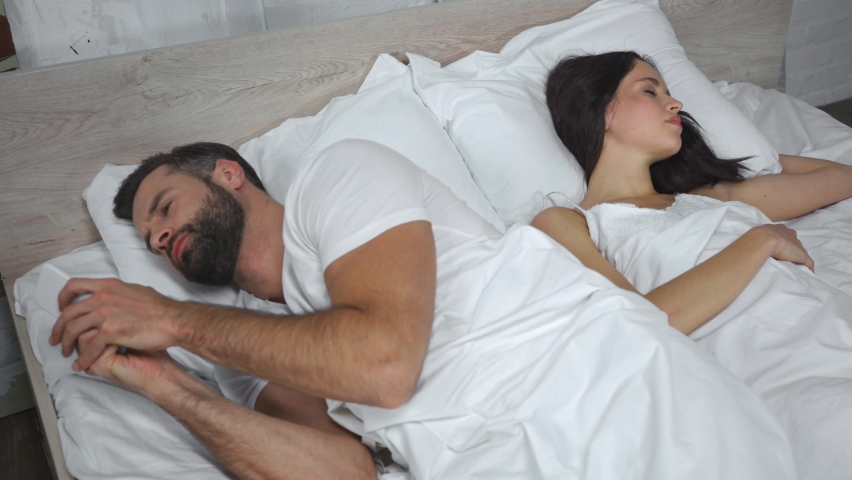 Bearded man texting on smartphone while looking and sleeping wife