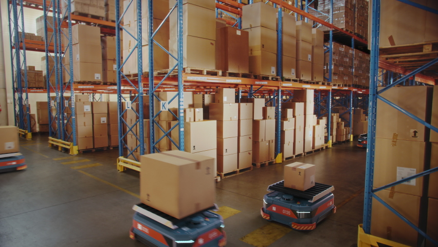 Future Technology: Automated Modern Retail Warehouse Delivery AGV Robots Transporting Cardboard Boxes in Distribution Logistics Center. Automated Guided Vehicles Delivering Goods, Products, Packages Royalty-Free Stock Footage #1065464995