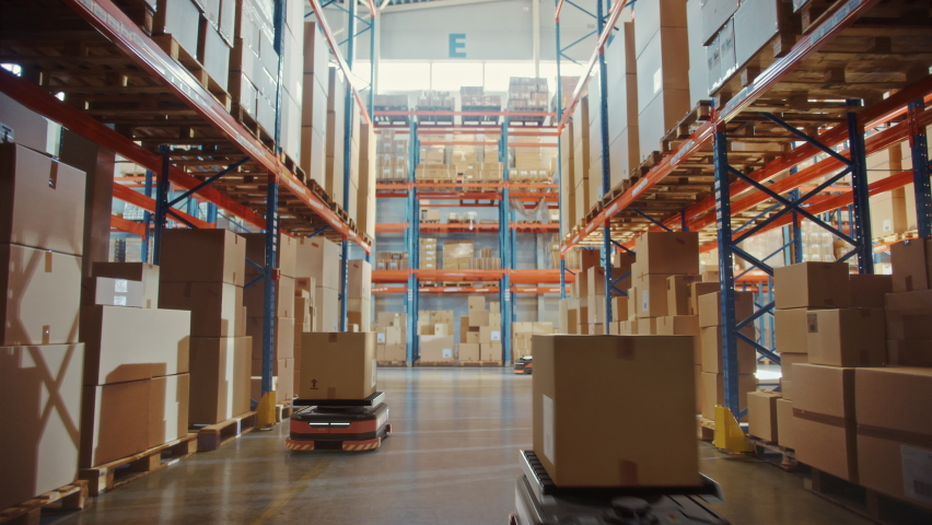 Future Technology 3D Concept: Automated Modern Retail Warehouse AGV Robots Transporting Cardboard Boxes in Distribution Logistics Center. Automated Guided Vehicles Delivering Goods, Products, Packages Royalty-Free Stock Footage #1065465031