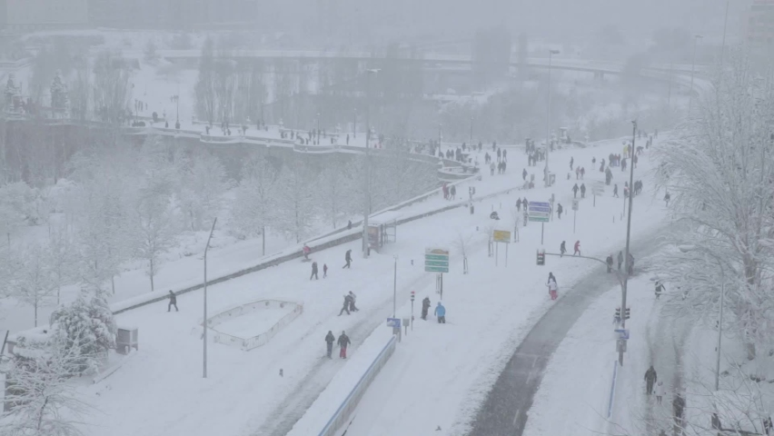 MADRID, SPAIN – January 10th 2021: Madrid Covered in Snow due to the Historic Filomena Weather Storm, People Walking during the Day while Snowing in the Capital of Spain, Landscape with Bridge