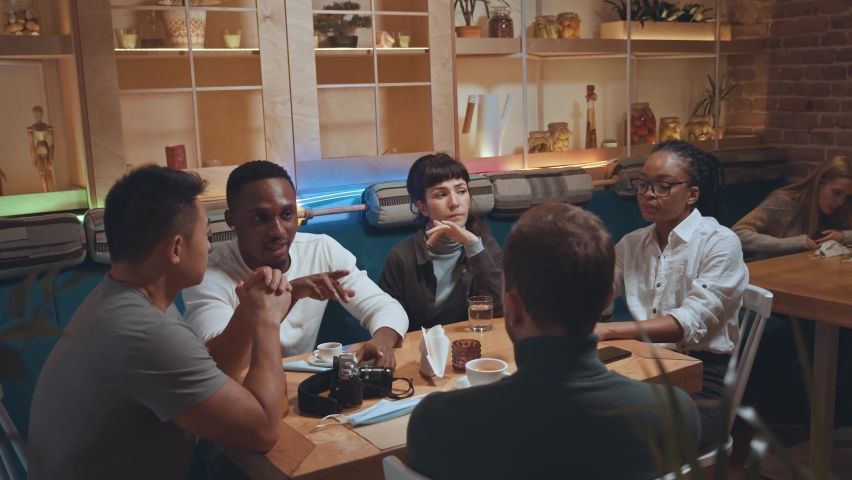 Happy multiracial diverse students or coworkers team studying or working together while share cafe table. People talking and laughing at funny joke while having fun and enjoy communication at meeting | Shutterstock HD Video #1065500893