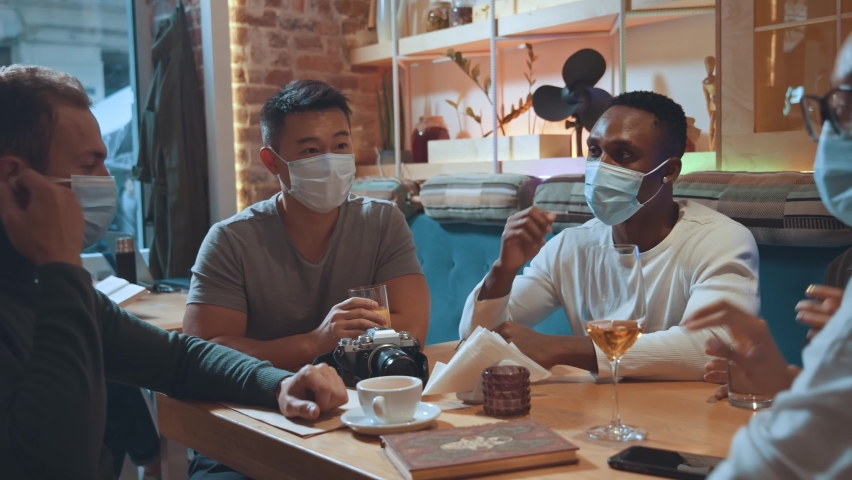 New normal. Happy diverse people taking off their protective masks while coming at the cafeteria. Multiracial friends preparing to drinking beverages and eating dishes at the cafe. Friendship concept Royalty-Free Stock Footage #1065500911