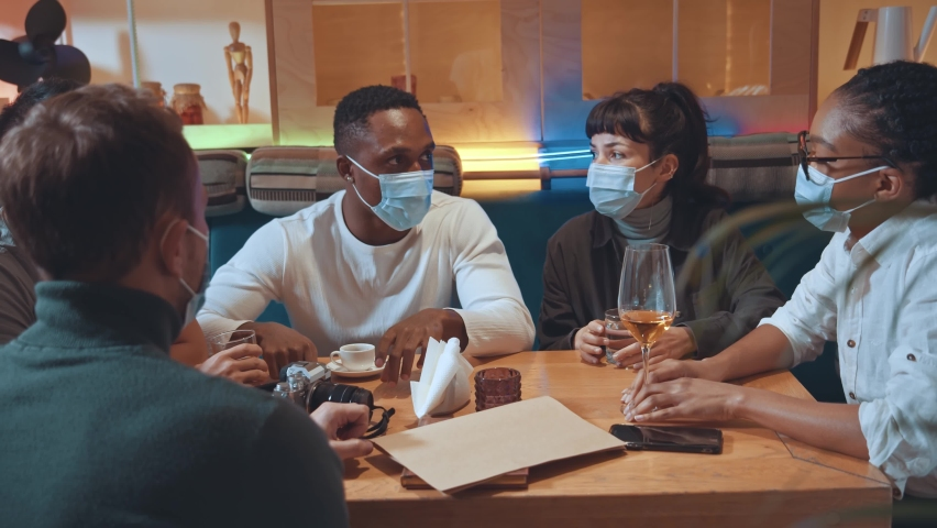 Happy multiracial diverse students team wearing protective masks studying or working together at the cafe table. People talking while having fun and enjoy communication at group meeting at restaurant Royalty-Free Stock Footage #1065500914