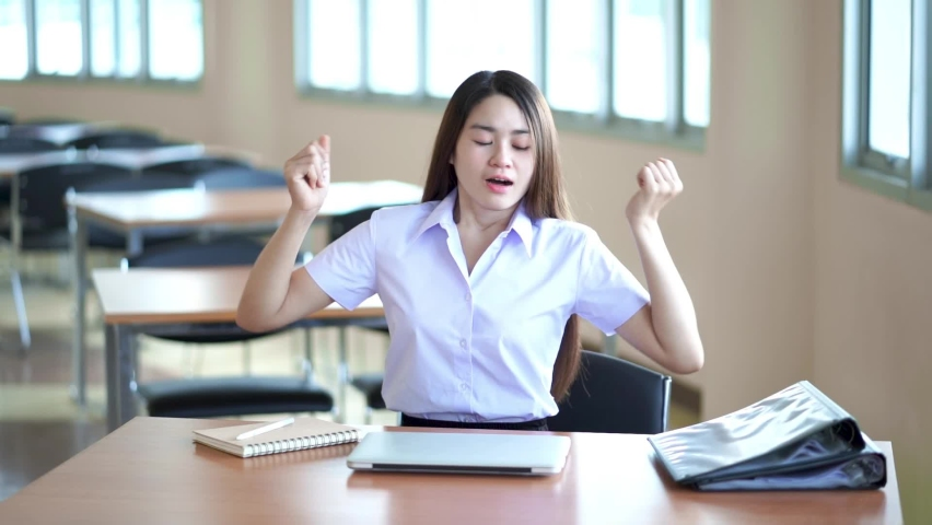 Young students folding laptop Then use the posture to relax the body that is tired from work for a long time.