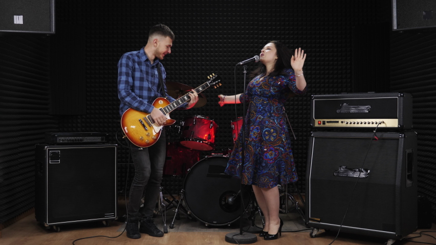 Two musicians are rehearsing at vocal recording studio, singing songs, dancing and having fun. Female singer sings to accompaniment of guitar. Music band plays jazz fun music   Shutterstock HD Video #1065523450
