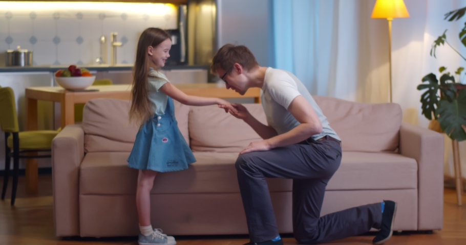 Loving father kneeling and kissing little daughter hand playing together at home. Side view of man standing on one knee and holding hand of cute preteen child Royalty-Free Stock Footage #1065536461