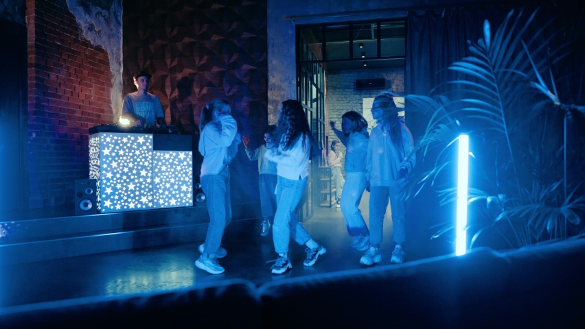 The DJ guy is playing vinyl at the mixing console at a party. Teenagers dance at a disco in the rays of a discobolus and neon light. A few teenagers remain in the lobby.   Shutterstock HD Video #1065538732