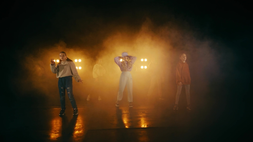 A group of teenage girls are actively moving to the music on the dance floor. The black floor and background of the dance studio, professional light and stage fog create a unique atmosphere.   Shutterstock HD Video #1065538750