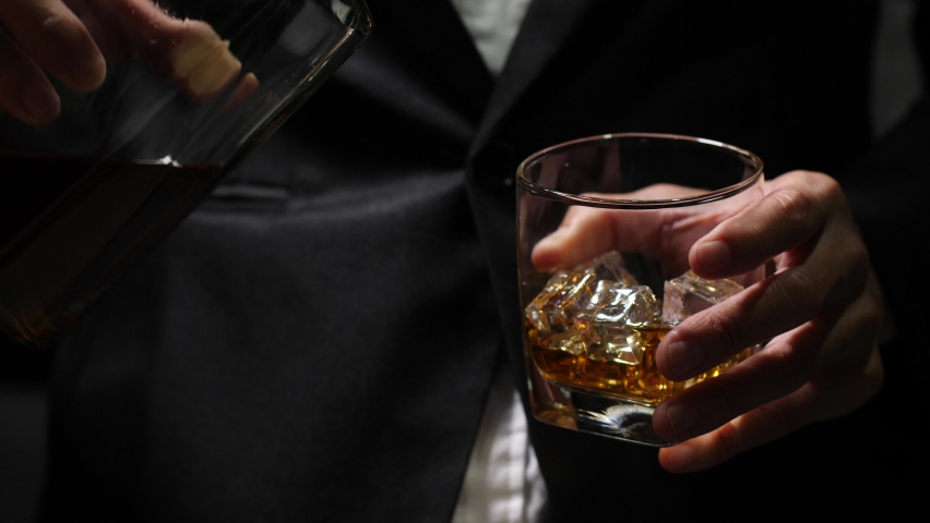 Businessman holding and pouring a glass of whiskey.   Shutterstock HD Video #1065549916