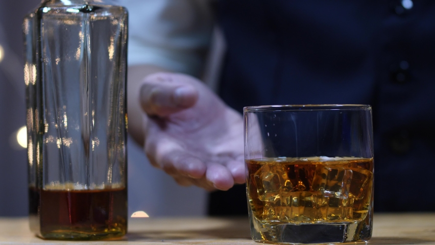 Barman moves whiskey glass in the beautiful night.   Shutterstock HD Video #1065549922
