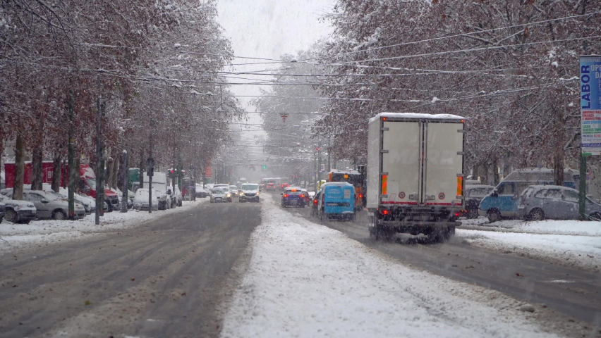 The movement of the car on a snowy day and evening in the city. Snowfall in the city. Street lights and snow-covered cars. City road in the snow. Car traffic. Italy, Milan, December 2020: