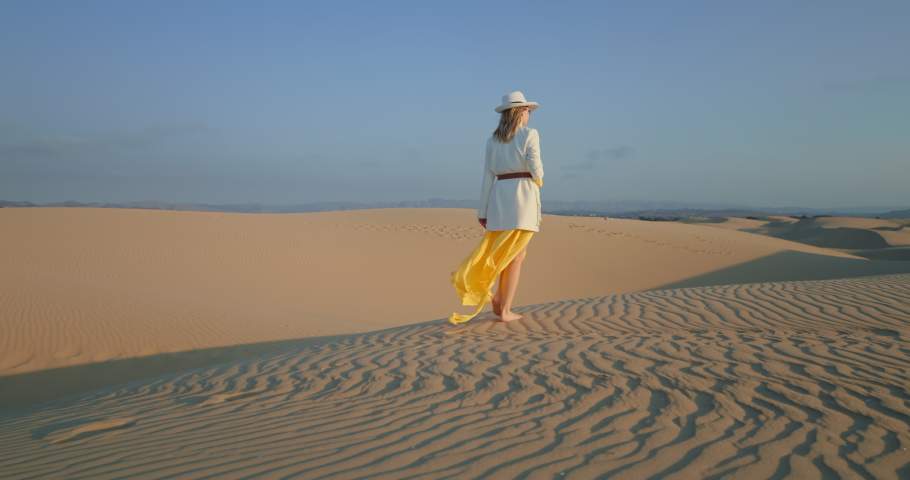 Fashionable woman in hat looking around desert landscape. Attractive girl exploring wild nature of desert. Romantic lady wearing yellow dress waving by wind in slow motion, 4k footage | Shutterstock HD Video #1065556954