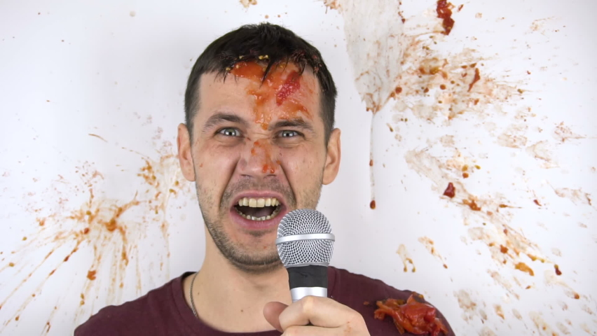 Viewers throw rotten tomatoes at a failed stand-up comedian. A young attractive guy gets hit in the face by a rotten tomato in slow motion.   Shutterstock HD Video #1065559786