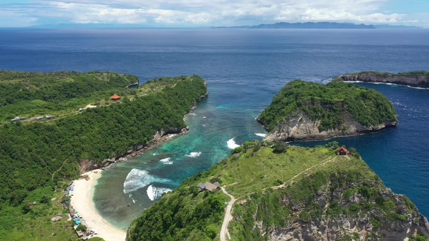 Aerial drone footage of the stunning Atuh beach in the Nusa Penida island off the coast of Bali in Indonesia, Southeast Asia. Shot with a rotation and tilt down motion   Shutterstock HD Video #1065573217
