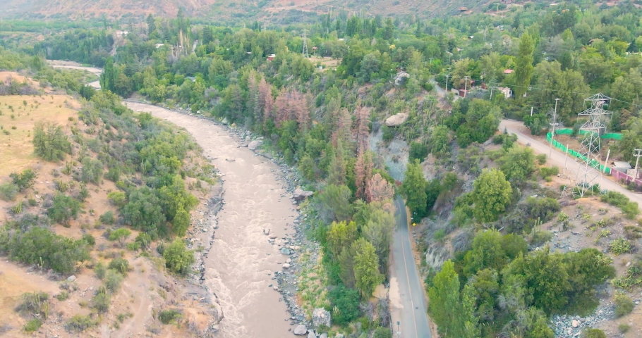 Aerial view over the Camino al Volcan route at Cajon del Maipo of a car passing by   Shutterstock HD Video #1065573424