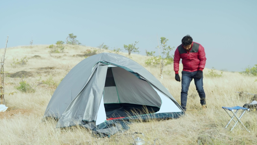 Traveler packing or closing tent on top of mountain - concept of recreation, travel and tourism in mountains during weekend or vocations