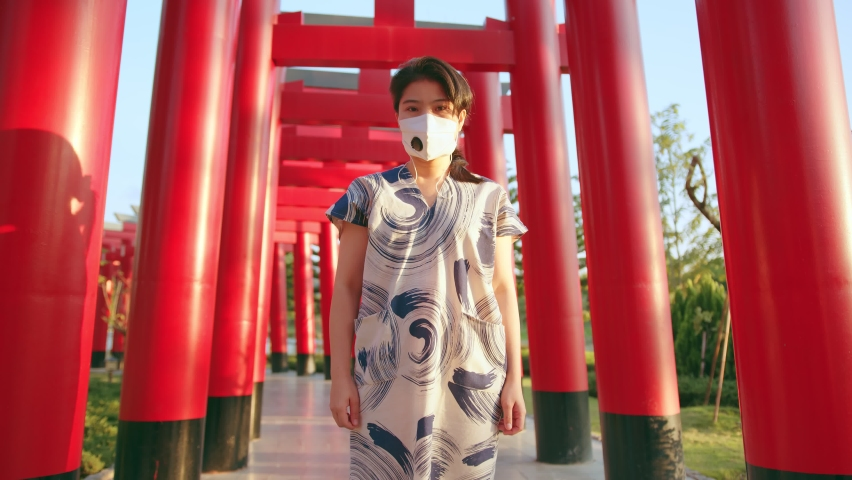 Young attractive asian female wearing face mask virus protective at japan tradition temple safety travel new normal lifestyle | Shutterstock HD Video #1065585964