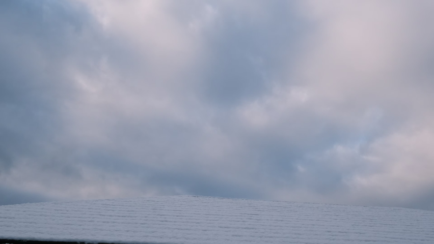 Snow-covered roof and winter sky. | Shutterstock HD Video #1065588100