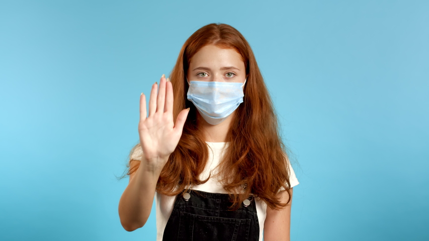 Pretty woman in protective mask disapproving with NO hand sign gesture. Denying, rejecting, disagree, portrait of beautiful girl or student on blue background | Shutterstock HD Video #1065588535
