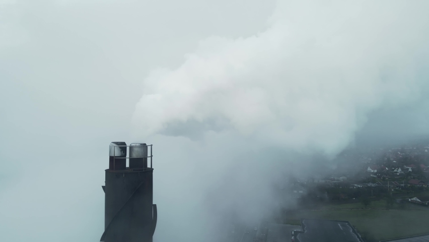 White smoke streaming out of a large industrial smoke stack at a factory. Close up aerial footage.   Shutterstock HD Video #1065596038