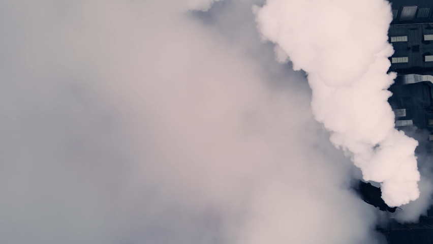 Dense white smoke and steam coming from a large manufacturing plant. Top down aerial footage.   Shutterstock HD Video #1065596260