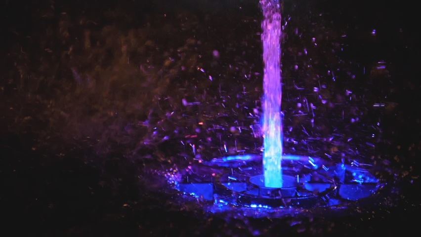 Splashes of fountain. Slow motion of water illuminated in colorful falling on fountain which change it water color in night. Wonderful multicolored fountain throws up high streams of sparkling water.   Shutterstock HD Video #1065598309